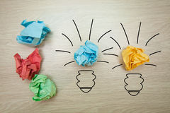 The concept, the idea of colored paper. Crumpled drawn light bulb on wooden background for business presentations Royalty Free Stock Photo