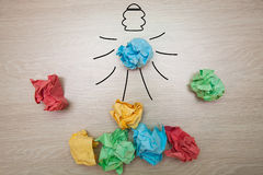 The concept, the idea of colored paper. Crumpled drawn light bulb on wooden background for business presentations Royalty Free Stock Photos