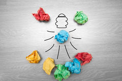 The concept, the idea of colored paper. Crumpled drawn light bulb on wooden background for business presentations Stock Photography