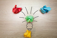 The concept, the idea of colored paper. Crumpled drawn light bulb on wooden background for business presentations Royalty Free Stock Photography