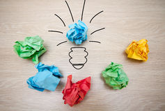 The concept, the idea of colored paper. Crumpled drawn light bulb on wooden background for business presentations Stock Photo