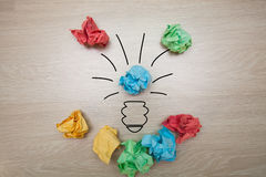 The concept, the idea of colored paper. Crumpled drawn light bulb on wooden background for business presentations Stock Image