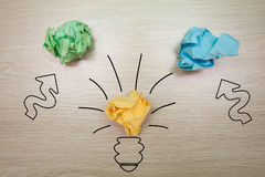 The concept, the idea of colored paper. Crumpled painted lamp with arrows on a wooden background for business presentations Royalty Free Stock Image