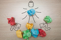 The concept, the idea of colored paper. Crumpled painted lamp with arrows on a wooden background for business presentations Royalty Free Stock Images
