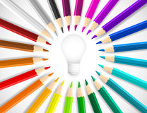 Concept idea with colorful  pencils as beams around lightbulb icon. On grey background Stock Image