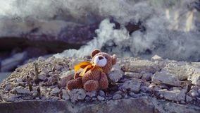 Concept idea of disaster victims ,toy bear falls on the background of Smoking ruins