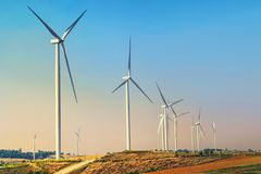 concept idea eco power energy. wind turbine on hill with stock images