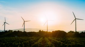 Concept idea eco power energy. wind turbine on hill with sunset royalty free stock images