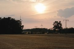 Concept idea eco power energy. wind turbine on hill with sunset stock photo