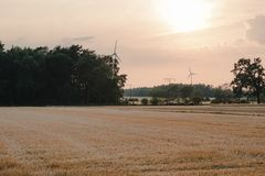 Concept idea eco power energy. wind turbine on hill with sunset royalty free stock image