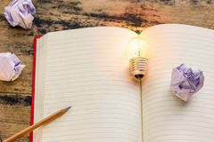 Concept idea. Growing light bulb on vintage book with crumpled p. Apers and pencil. Copy space for your text. conceptual great ideas are always available royalty free stock image