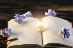 Concept idea. Growing light bulb on vintage book with crumpled p. Apers and pencil. Copy space for your text. conceptual great ideas are always available royalty free stock photography