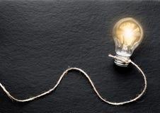 Concept of idea illustration lit lamp on black background Stock Images