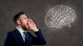 A man screams at the brain. Concept idea, solution. A man screams at the brain stock image