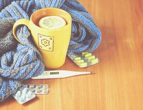 Concept illness, colds, cure, fall and winter. Tea with lemon, thermometer, pills and a knitted blanket Royalty Free Stock Photo