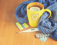 Concept illness, colds, cure, fall and winter. Tea with lemon, thermometer, pills and a knitted blanket Stock Image