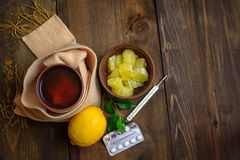 Concept illness, colds, cure, fall and winter. Tea with lemon, thermometer, pills and a knitted scarf. Top View. Stock Photos