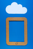 A concept illustration of cloud storage. A paper illustration of an cardboard tablet pc on a bright blue background with white cloud above depicting a concept of Stock Image