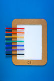 A concept illustration of tablet pc with drawing application run. A paper illustration of an cardboard tablet pc on a bright blue background with color pens vector illustration