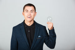 Concept image of a businessman holding bulb Royalty Free Stock Images