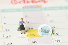 Concept image of a Calendar. Closeup shot of a thumbtack attached. The words Dinner written on a white notebook to remind you an stock photo