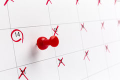 Concept image of a Calendar with red push pin. Closeup shot thumbtack attached. The words heart shape written on white. Concept image of a Calendar with a red Stock Photography