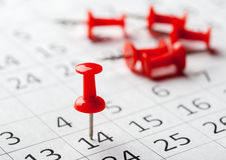 Concept image of a calendar with red push pins Royalty Free Stock Photos