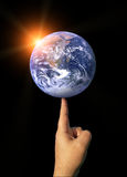 Concept Image of The Earth Balancing on a Finger Royalty Free Stock Photos