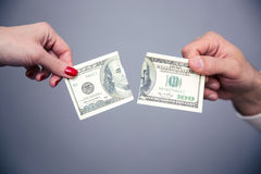 Concept image of a female and male hand dividing money Stock Photos