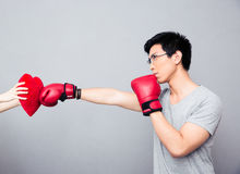 Concept image of a man in boxing gloves hitting at heart Stock Photos