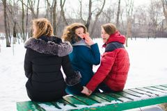 The concept of the image of marital infidelity. Young people on the bench, hugs one and hold the other`s hand royalty free stock photography