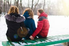 The concept of the image of marital infidelity. Young people on the bench, hugs one and hold the other`s hand royalty free stock image