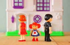 Concept image of parent busy or angry and child in the middle in front of. little plastic toy dolls (male , female, child) , selec Royalty Free Stock Photo