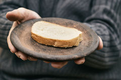Concept image for poverty. Old man's hands holding rustic plate with one slice of bread. Concept image for poverty Royalty Free Stock Images