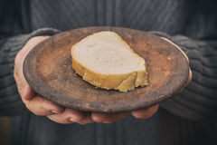 Concept image for poverty. Old man's hands holding rustic plate with one slice of bread. Concept image for poverty Stock Image