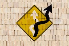 Concept image: searching for alternatives. Sinuous arrow of traffic sign emerging from the plate in new direction, stamped on pil of bricks, like a graffiti Stock Photos