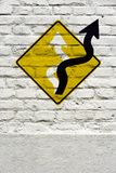 Concept image: searching for alternatives. Sinuous arrow of traffic sign emerging from the plate in new direction, stamped on white brick wall, like a graffiti Stock Images