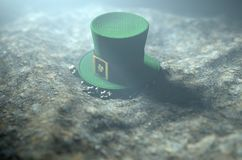 Lost Tiny Leprechaun Hat. A concept image showing a tiny leprechaun hat apparently lost on the ground at night - 3D render Stock Photo