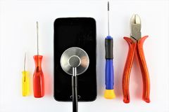 An concept image of a smart phone diagnostic with gadgets and a stethoscope Royalty Free Stock Image