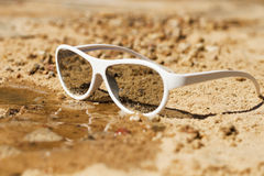 Concept image of summer holidays with beach scene in sunglasses on sand Royalty Free Stock Images