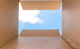 Concept image `Thinking Outside the Box`. Lateral Thinking for Innovation - Inside a cardboard box with clear sky and cloud -The Light at the End of the Way stock photos