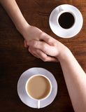 Concept image of two bonded hands and coffee Royalty Free Stock Images