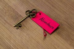 Key to abundance. Concept image using a key and a tag with the word abundance handwritten on it over a wooden background royalty free stock images