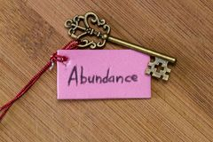 Key to abundance. Concept image using a key and a tag with the word abundance handwritten on it over a wooden background stock photo