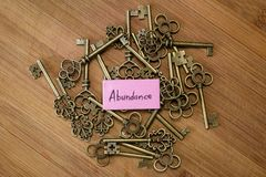 Keys to abundance. Concept image using old keys and a tag with the word abundance handwritten on it over a wooden background royalty free stock photos