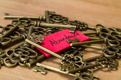 Keys to abundance. Concept image using old keys and a tag with the word abundance handwritten on it over a wooden background stock photos