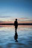 Concept image of young boy walking on water in sunset landscape Stock Images
