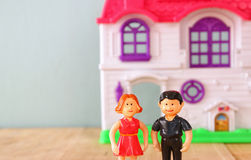 Concept image of young couple in front of new house. little plastic toy dolls (male and female) , selective focus. Royalty Free Stock Image