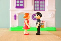 Concept image of young couple in front of new house. little plastic toy dolls (male and female) , selective focus. Royalty Free Stock Photography