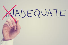 Concept of Inadequate versus Adequate. With a business man crossing through the In in the word Inadequate with a red pen on a virtual screen with blank white Royalty Free Stock Photography